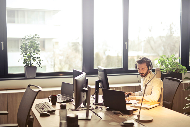 A man is sitting at a desk on the phone and looking at a computer. He works for an outsourced IT department.