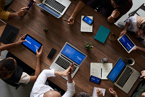 A company gathered around a table with many laptops open, symbolizing how they need to outsource an IT company for the numerous security precautions
