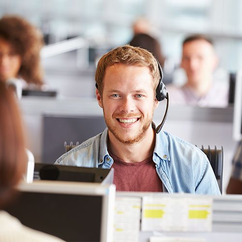 Man works at computer providing IT support.