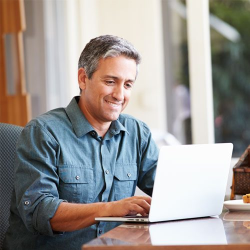 A middle-aged man smiling while working on his laptop.