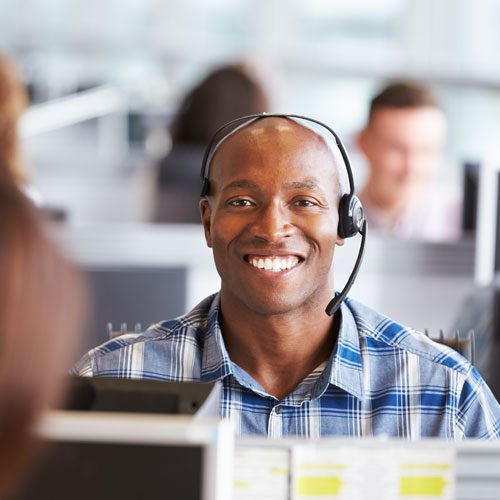 A man smiling with a headset on, providing IT support.